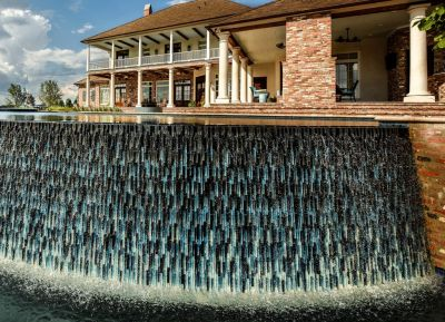 Project after project, making incredible complexity seem routine is what Jimmy Reed and his tile installers are all about.  That  unwavering finesse is particularly on display in this sublime poolscape, with its tilting, undulating vanishing-edge wall and uniquely configured spillover spa.