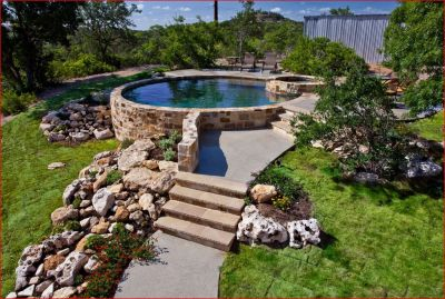 """Natural materials accentuate almost any design, like the way the stone and grassy slope embrace this circular pool and spa. The grass is an important part of the """"material"""" palette I use create an attractive and welcoming sense of place."""