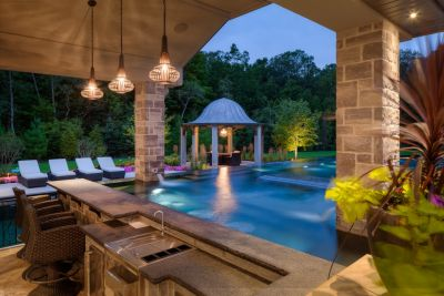 With winter slowly ending, Barry Justus knew that he had no time to spare in converting this homeowner's dream of a personal five-star resort into a multi-watershape, party-ready reality.  This included the hidden slide and the vanishing television -- all on a rigid deadline.