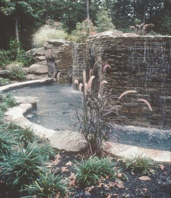 Set in an affluent neighborhood in Cherry Hill, N.J., this project offered the Liquid Designs team a golden opportunity to transform a dull, aimless front yard into a sublimely beautiful and uniquely engaging environment.  Here, designers David Tisherman and Kevin Fleming share a few words and a number of photographs that show just what they were after in using water, plants and masonry to exploit the power and drama of surprise.