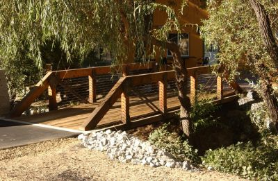 The art and craft of building wooden bridges has been overtaken through the years, with steel and reinforced-concrete structures almost entirely supplanting them for the past 100 years or so.  But designer/builder Dan Moosman has bucked the modern trend, providing his clients with Craftsman-style wooden bridges that now grace landscapes across the country and make strong aesthetic statements wherever they're placed.