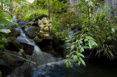 With equal doses of patience and understanding, observes garden artist Rick Driemeyer, great watershapes and gardens can emerge from extended periods of close interaction between designers and their clients.  A case in point is the project shared here, where long acquaintance with his clients' wants and needs enabled him to transform a compact teahouse/pond/waterfall composition into a finely decorated, highly personalized sanctuary.