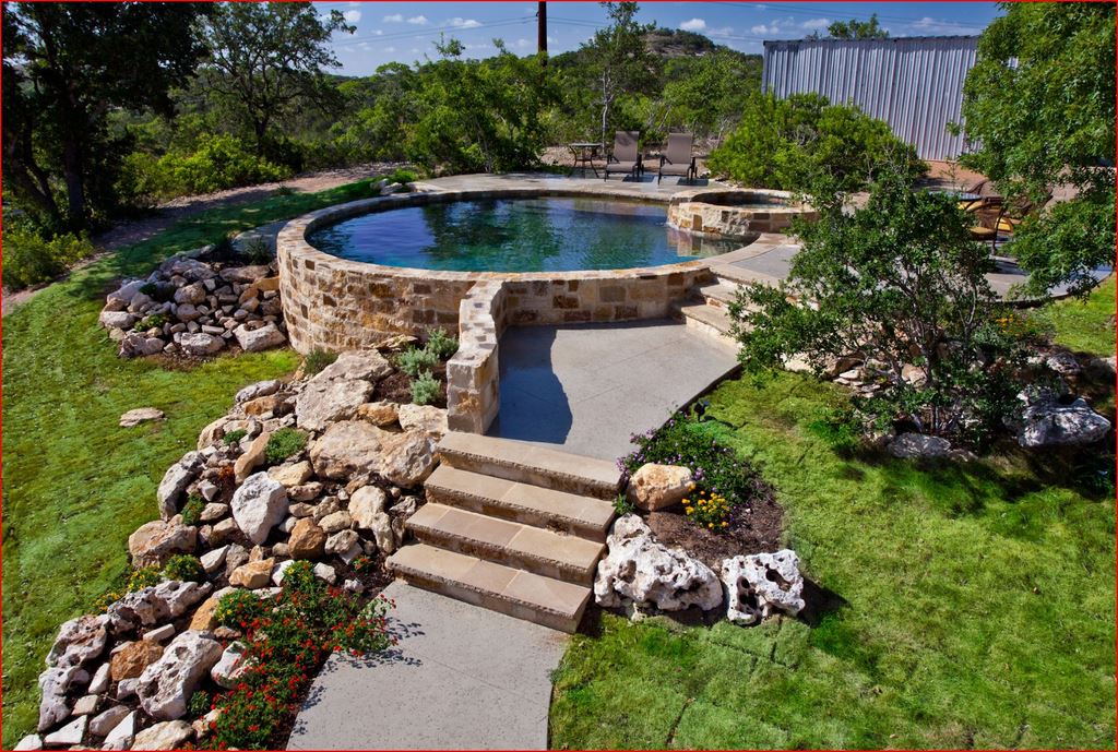 Natural materials accentuate almost any design, like the way the stone and grassy slope embrace this circular pool and spa. The grass is an important part of the